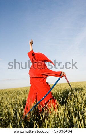 Spooky figure in red hood with a scythe - stock photo