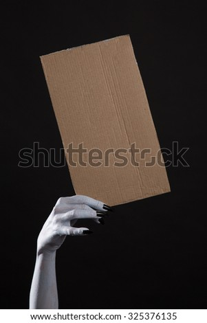 Spooky ghost hand with black nails holding blank cardboard, Halloween theme  - stock photo