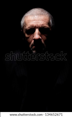 Spooky grey haired mature man with black-out eyes - stock photo