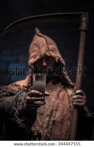 Spooky grim Reaper is proposing you to drink a glass of alcohol. He is standing and looking forward with treats. The man is holding a scythe - stock photo