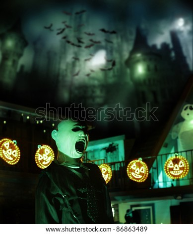 Spooky Halloween concept image of scary castle and bats in background with glowing pumpkins and monster in foreground - stock photo