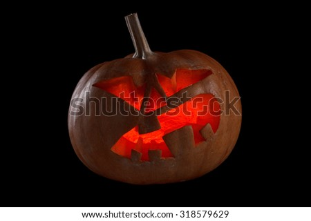 Spooky halloween pumpkin Jack O Lantern shiny inside on black. Isolated on black background - stock photo