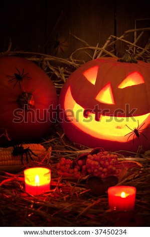 Spooky Halloween pumpkin with lit candles in the barn with spiders crawling in the straw - stock photo