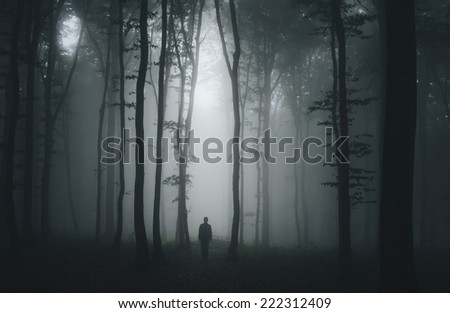 spooky halloween scene with man in dark forest - stock photo