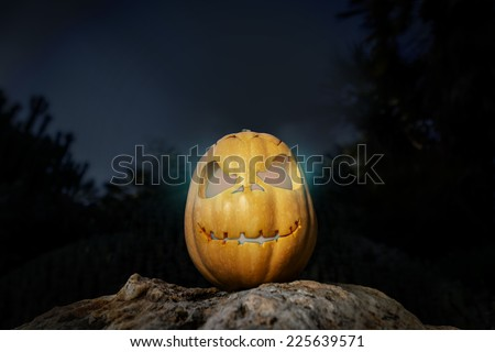 Spooky Halloween warm neon and scary pumpkin jack-o-lantern with a smile on a rock from bottom perspective template illustration from the darkness - stock photo