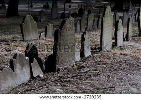 spooky looking moss covered tomb stones on a beautiful winter's afternoon - stock photo