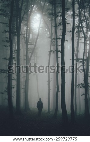 spooky man silhouette in dark forest - stock photo