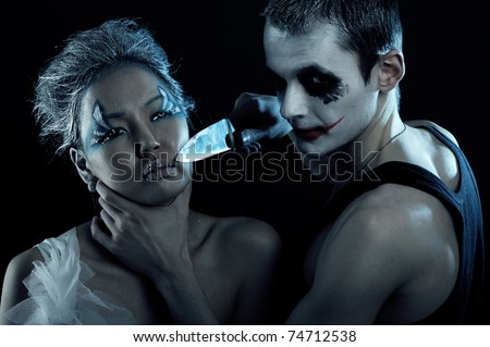 Spooky man with knife in darkness - stock photo
