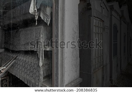 Spooky old european cemetery chapel with funeral urns covered with embroidered quilts  - stock photo
