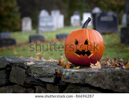 Spooky pumpkin with graveyard background in Fall - stock photo