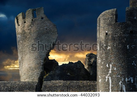 Spooky ruined castle lit by sunset and bright moonlight - stock photo