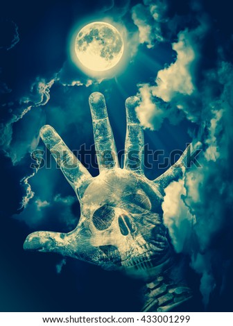 Spooky skull combined with dirty palm on nightly sky and clouds with bright full moon for halloween background. Hand up to sky. The moon taken with my own camera, no NASA images used. Cross process. - stock photo
