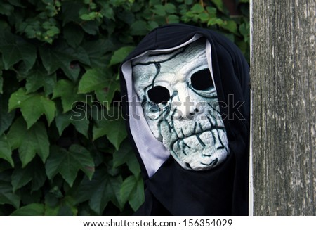 spooky skull  mask looking around a telephone pole - stock photo