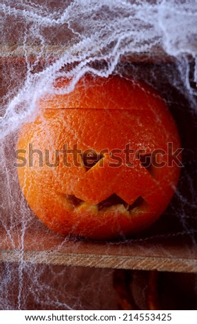 Spooky spider web covered jack-o-lantern formed from a fresh orange on a wooden shelf in a scary Halloween background - stock photo