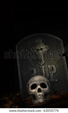 Spooky tombstone with skull on black background - stock photo
