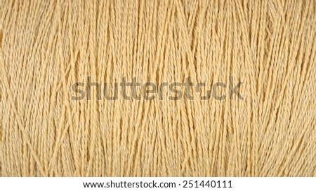 Spool of beige thread macro background texture - stock photo