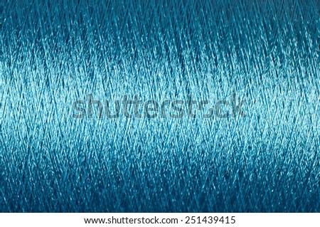 Spool of blue thread macro background  - stock photo