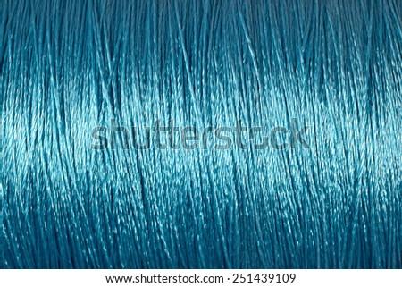 Spool of blue thread macro background texture - stock photo