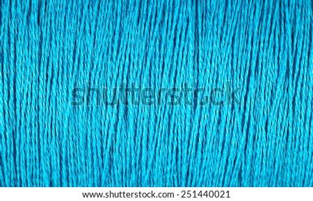Spool of blue thread macro texture - stock photo
