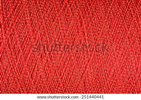 Spool of orange thread macro background - stock photo