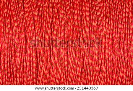 Spool of orange thread macro background texture - stock photo