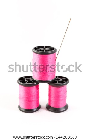 Spool of pink thread and needle - stock photo