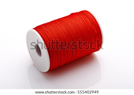 Spool of professional red threads on a white background