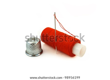 spool of red thread with a needle and thimble - stock photo