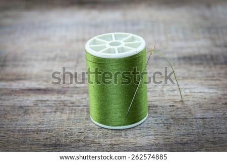 Spool of thread and needle on wood. - stock photo
