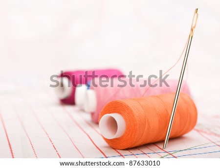 Spool of thread and needle. Sew accessories on blurred background. - stock photo