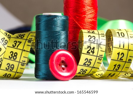 Spool of thread and sewing accessories - stock photo