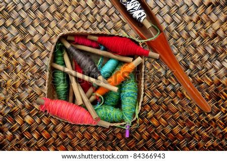spool of thread and shuttle of thai cloth weaving machine - stock photo