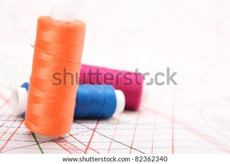 Spool of thread. Sew accessories on blurred background - stock photo