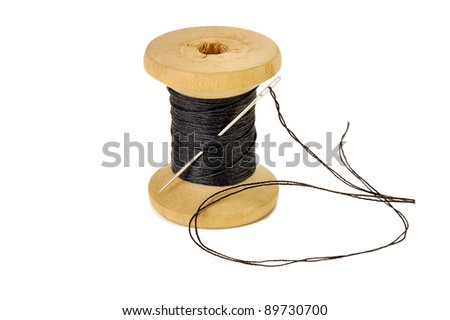 spool of thread with a needle closeup on white background - stock photo