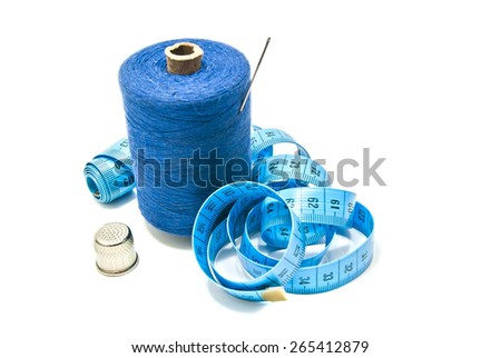 spool of thread with needle, meter and thimble on white - stock photo