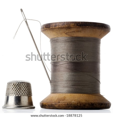 spool of thread with needle stuck in and thimble on white - stock photo