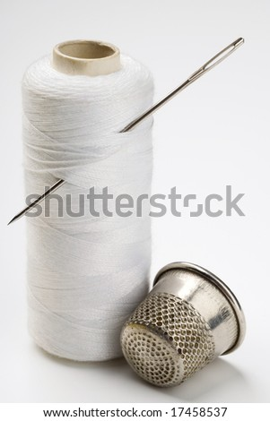 spool of thread with needle stuck in it and a thimble - stock photo