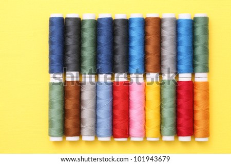 Spool of threads on yellow background - stock photo