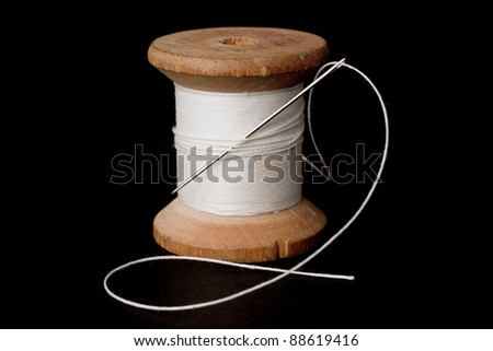 Spool of white thread and a needle over a black background - stock photo