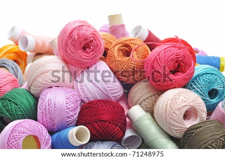 spools and balls of yarn of many colors on a white background - stock photo