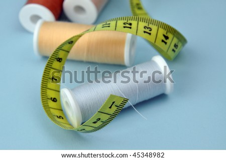 Spools and measuring tape on a blue background