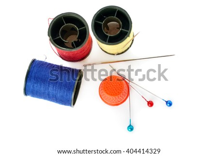 Spools of different threads, thimble and needles isolated over the white background, as sewing composition - stock photo
