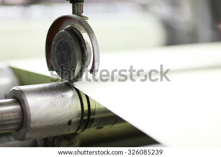 Spools of paper .Working print machine. selective focus on metal shafts and screws - stock photo
