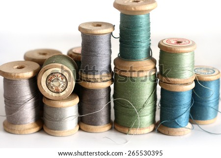 Spools of thread on a white background. Old sewing accessories. colored threads - stock photo
