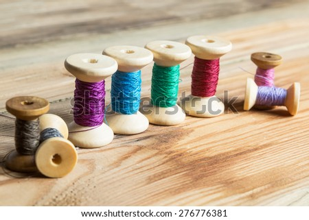 Spools of thread on wooden  background. Old sewing accessories. colored threads - stock photo