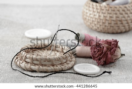 Spools of thread with needle and sewing buttons - stock photo