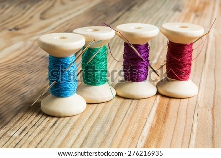 Spools of thread with needles on wooden background. Old sewing accessories. colored threads - stock photo