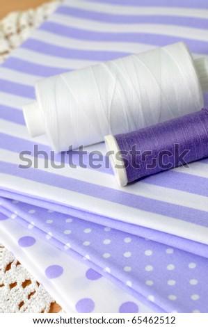 Spools on purple cloth - stock photo