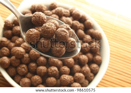 Spoon and bowl with chocolate balls. - stock photo