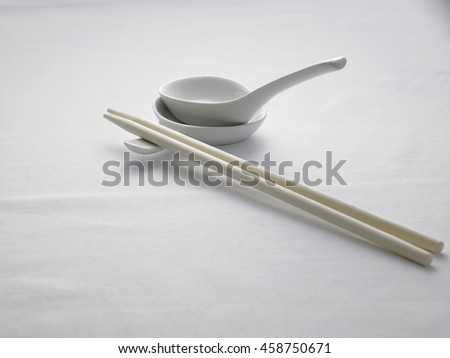 spoon and chopsticks on top of white table cloth